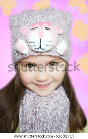 Beautiful little girl in cap and scarf - stock photo
