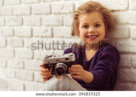 Beautiful little girl in casual clothes is holding a camera, looking at camera and smiling, sitting against white brick wall - stock photo