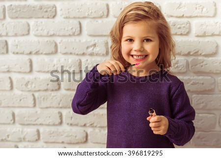 Beautiful little girl in casual clothes is holding a lipstick, looking at camera and smiling, standing against white brick wall - stock photo