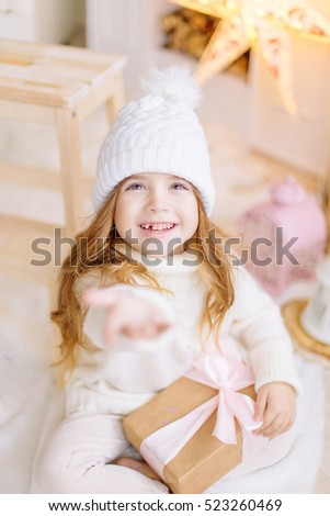 Beautiful little girl in christmas decoration wearing winter hat