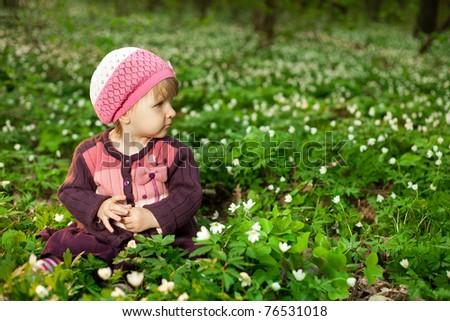 beautiful little girl in forest on flowers field - stock photo