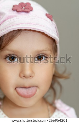Beautiful little girl in hat shows tongue. - stock photo