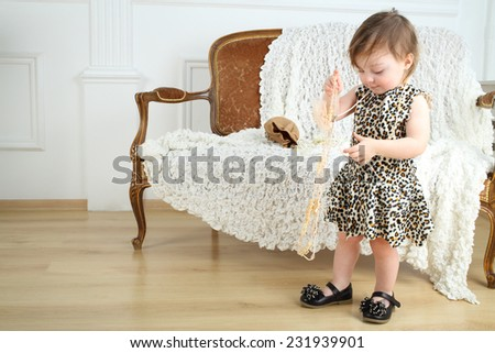 Beautiful little girl in leopard print dress with beads stands near sofa in room - stock photo