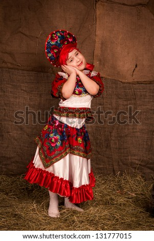 Beautiful little girl in national costume dancing