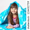 beautiful little girl in pajamas lying in bed under a blue blanket - stock photo
