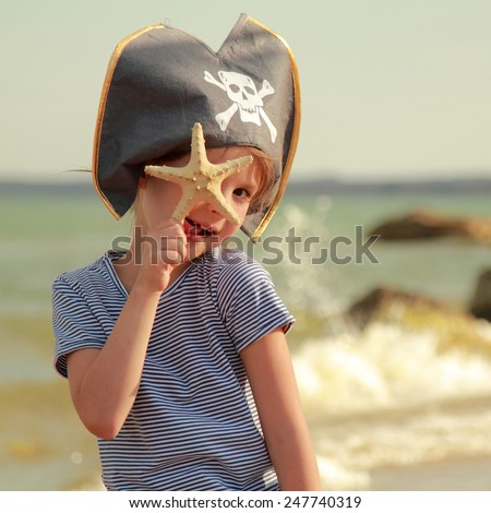 Beautiful little girl in pirate hat with a skull holding a starfish on the beach - stock photo