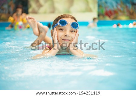Beautiful little girl in pool water park. - stock photo