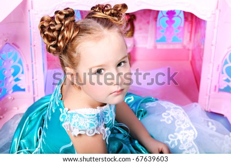 Beautiful little girl in princess dress playing with her toy castle. - stock photo