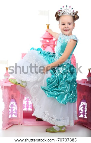 Beautiful little girl in princess dress playing with her toy castle. Isolated over white background. - stock photo