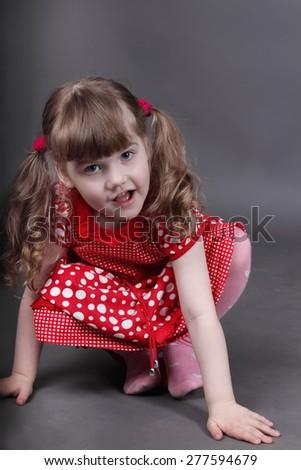 Beautiful little girl in red dress sits on floor in grey studio - stock photo
