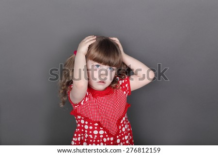 Beautiful little girl in red dress touches her head in grey studio - stock photo