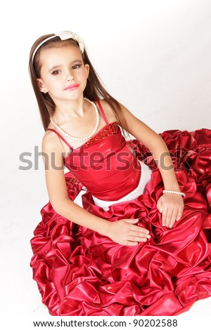 Beautiful little girl in red evening dress on white background