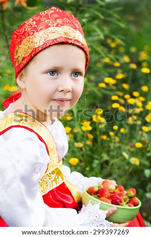 Beautiful little girl in russian costume with strawberry - stock photo