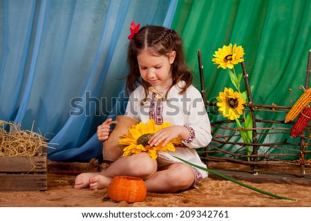 Beautiful little girl in Russian national dress in a rustic interior, Ukraine, Russia, indoors - stock photo