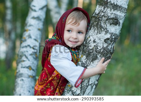 Beautiful little girl in russian traditional clothes in nature.Little cute girl in Russian national clothes.Traditional Russian folk costume.Portrait of a cute little girl outside - stock photo