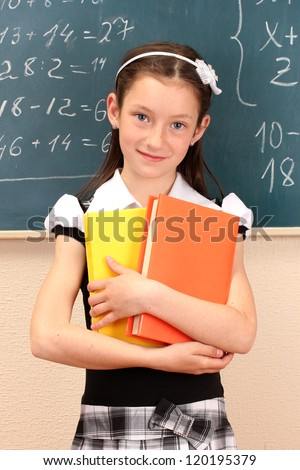 beautiful little girl in school uniform with books in class room
