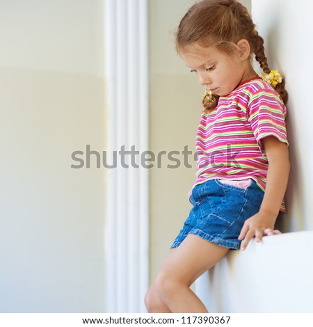 Beautiful little girl in shorts sitting on stone ledge, and sad.