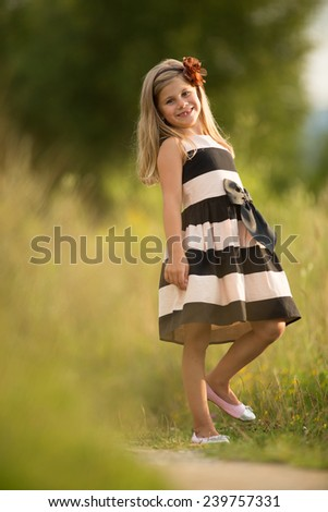 Beautiful little girl in striped dress posing and smiling to a camera in summer outdoors.  Adorable young girl smiling.  - stock photo