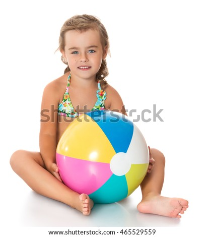Beautiful little girl in swimsuit. Girl holding in hands in front of a large striped ball. Girl sitting on the floor-Isolated on white background