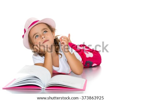 Beautiful little girl in the pink hat lying on the floor and reading a book - Isolated on white background - stock photo
