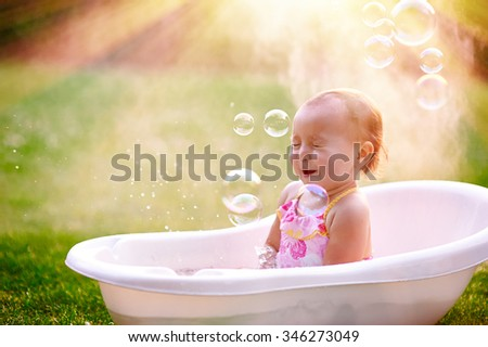 beautiful little girl in the summer bathing with soap bubbles. - stock photo
