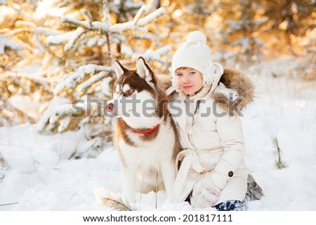 beautiful little girl in winter forest with dog - stock photo