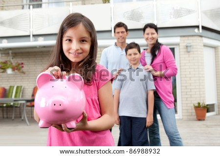 Beautiful little girl inserting coin in a piggy bank with her family in background - stock photo