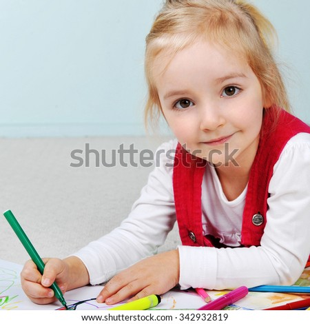 Beautiful little girl is drawing  on paper - stock photo