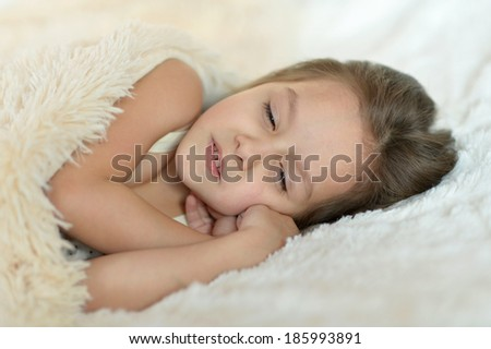 Beautiful little girl is sleeping in her bed at home
