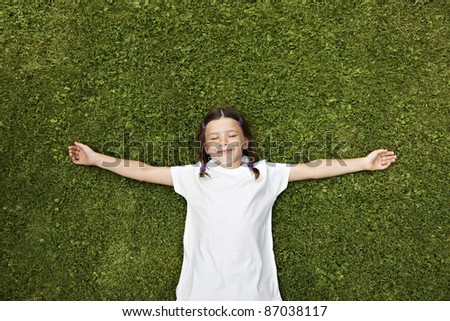 Beautiful little girl laying dreaming in grass - stock photo