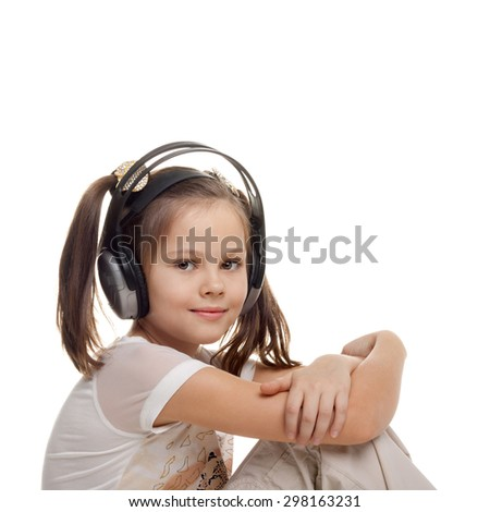 beautiful little girl listening to music in the headphones