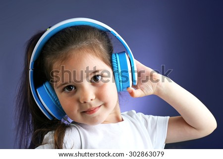 Beautiful little girl listening to music on color background - stock photo