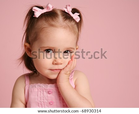 Beautiful little girl looking at the camera and posing on a pink background - stock photo