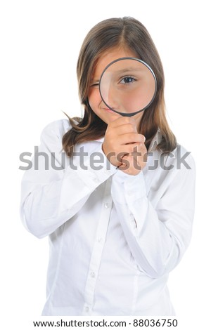 Beautiful little girl looking through a magnifying glass isolated on a white background