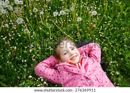 Beautiful little girl lying in grass, surrounded by dandelion seed heads, enjoying nature and its serenity. Natural childhood concept.  - stock photo