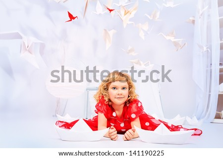 Beautiful little girl lying on a floor in her dream world surrounded with paper birds and ships. - stock photo