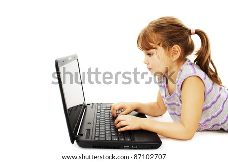 Beautiful little girl lying on floor with a laptop. Isolated on white background - stock photo