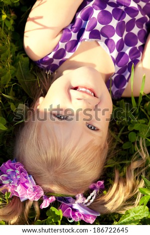Beautiful little girl lying on the grass in the park. Smiling child on a field with  flowers. Kid rest on the nature. Portrait of baby outdoor - stock photo