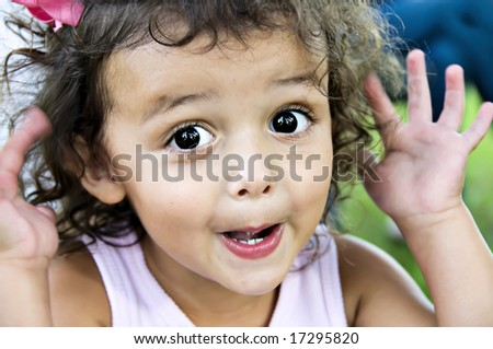 Beautiful little girl making a cute face with big, bold, brown eyes with  her hands by her face.