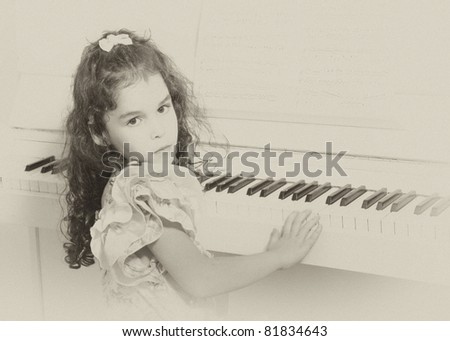 Beautiful little girl near a white piano (sepia, vintage style) - stock photo