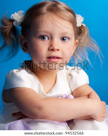 Beautiful little girl on a blue background - stock photo