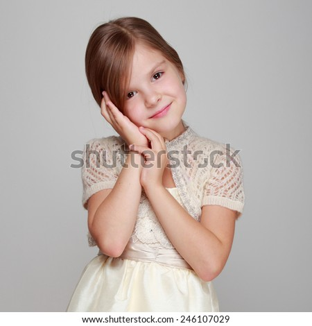Beautiful little girl on a gray background - stock photo