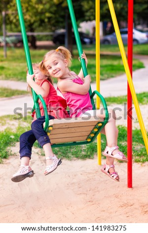 Beautiful little girl on a swings outdoor in the playground at summertime - stock photo