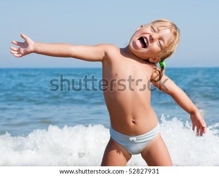 Beautiful little girl on beach on a sunny day - stock photo