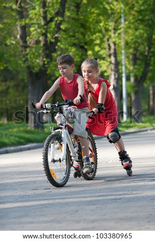 Beautiful little girl on   in-line skates following little boy on bicycle in a park at summer afternoon - stock photo