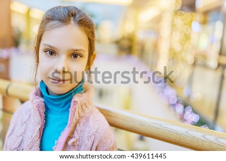 Beautiful little girl on the background of a large new shopping center. - stock photo