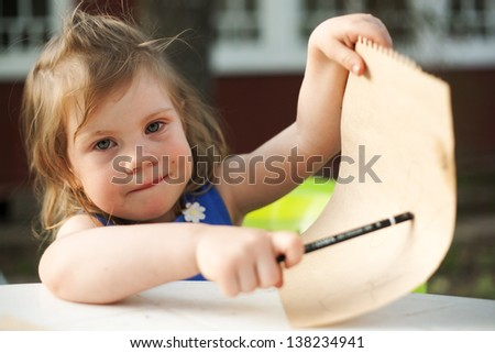 beautiful little girl on the summer background drawing