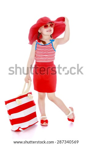 Beautiful little girl on vacation in a wide red hat and glasses holding a large beach bag-isolated on white background - stock photo
