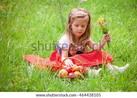 Beautiful little girl picking flowers in a meadow. Summer sunny day, lots of greenery and flowers