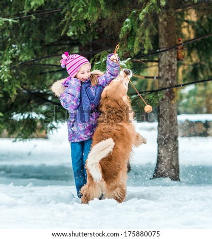 beautiful little girl play with her dog on the snow - stock photo